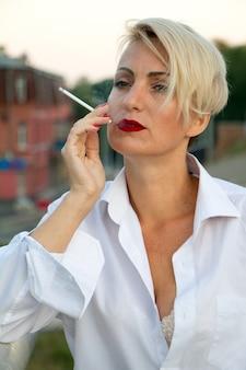 Piękna dojrzała blondynka w białej koszuli pali białego papierosa na zewnątrz w mieście w lecie