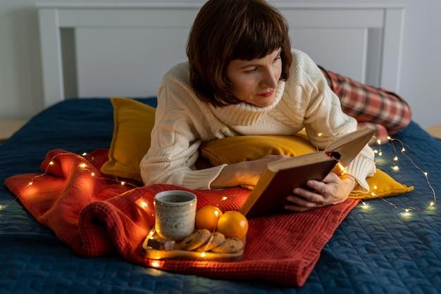 Piękna dojrzała kobieta czytanie książki. przytulny, wieczny relaks i refleksja.