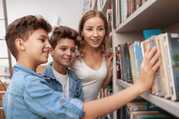 Piękna dojrzała kobieta i jej synowie bliźniacy wybierają książkę z półki w bibliotece