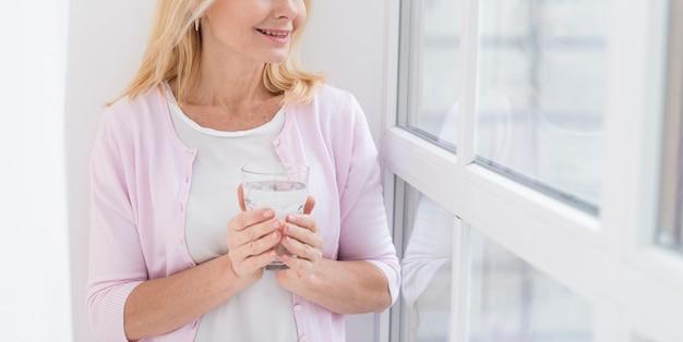 Piękna dojrzała kobieta pozuje z szkłem woda