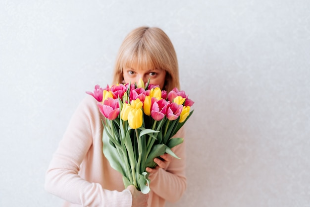 Piękna dojrzała kobieta trzyma tulipany