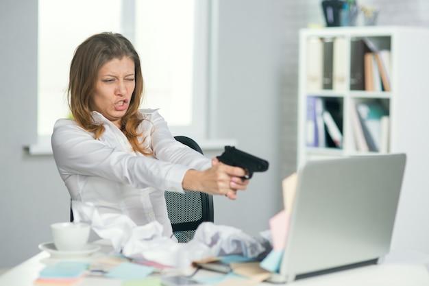 Piękna dojrzała kobieta w okularach z pistoletu strzelać w biurze. ciężko pracujący dzień już chce strzelać lub strzelać do komputera