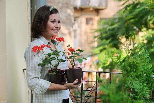 Piękna dojrzała kobieta z doniczkowymi czerwonymi lato kwiatami