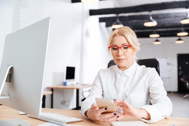 Piękna dojrzała kobieta za pomocą inteligentnego telefonu w biurze