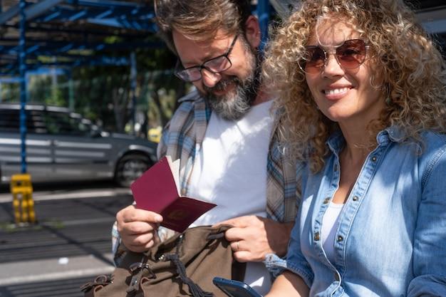 Piękna dojrzała para turystów na parkingu lotniska, przeglądająca dokumenty podróży i smartfon smart