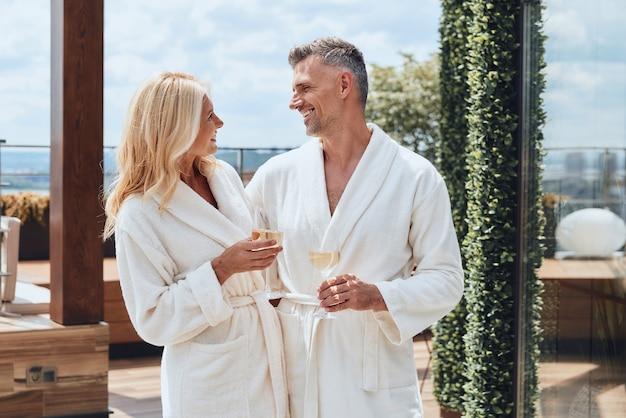 Piękna dojrzała para w szlafrokach delektuje się szampanem podczas relaksu w luksusowym hotelu na świeżym powietrzu