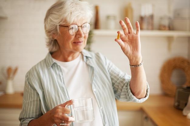 Piękna dojrzała sześćdziesięcioletnia kobieta w stylowych okularach trzymająca kubek i kapsułkę z suplementem omega 3, zamierzająca zażywać witaminę po posiłku. starszy siwy kobieta bierze pigułkę oleju z ryb wodą
