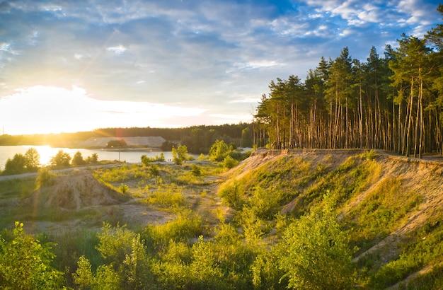 Piękna dolina z jeziorem i błękitnym niebem z dużymi chmurami i jasnym słońcem
