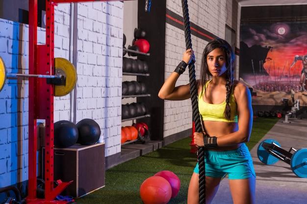 Piękna dopasowana dziewczyna na siłowni z czarną liną
