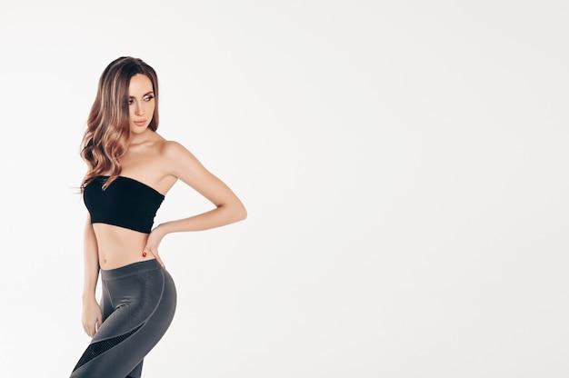 Piękna, dopasowana kobieta w czarnym garniturze siłowni
