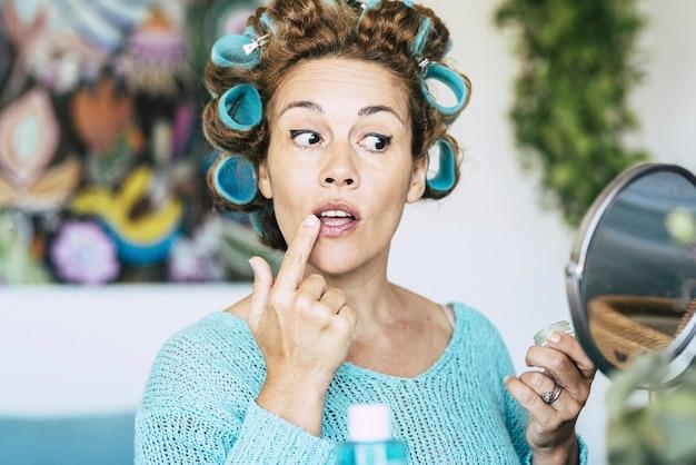 Piękna dorosła kaukaska kobieta w przygotowaniu się do domu, patrząc w lustro i z niebieskimi swetrami i lokówkami na włosach