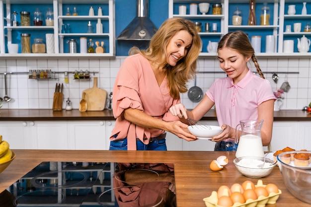 Piękna dorosła kobieta i córka do pieczenia w kuchni