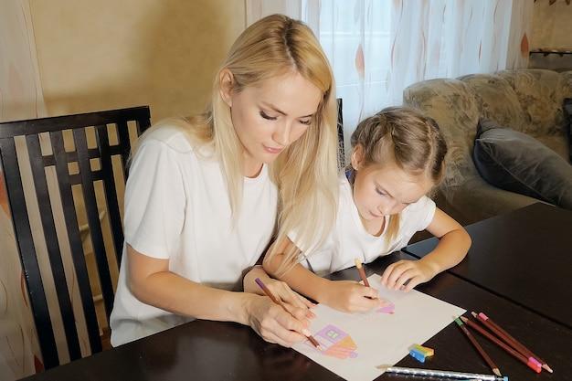 Piękna dorosła kobieta i dziewczyna malująca ołówkami na papierze siedząca przy stole w domu