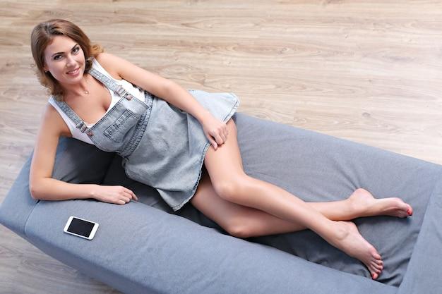 Piękna dorosła kobieta, leżąc na kanapie