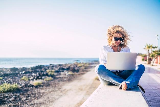 Piękna dorosła kobieta rasy kaukaskiej korzystająca z nowoczesnego laptopa na plaży na świeżym powietrzu