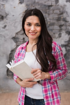 Piękna dorosła kobieta trzyma książkę