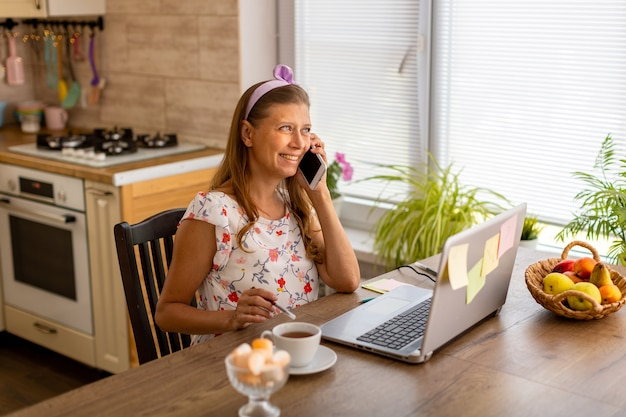 Piękna dorosła kobieta w domu w kuchni pracuje na laptopie i korzysta ze smartfona