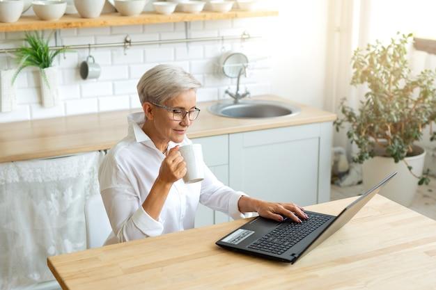 Piękna dorosła kobieta w okularach przy stole z laptopem w domu z kubkiem