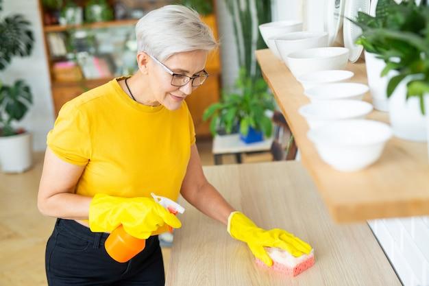Piękna dorosła kobieta w okularach w żółtej koszulce czyści dom