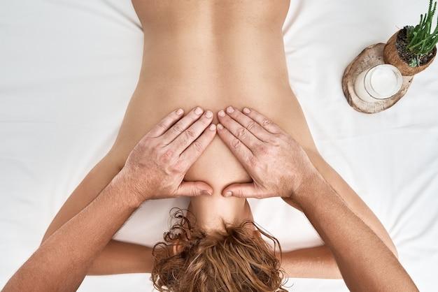 Piękna dorosła kobieta w salonie spa z profesjonalnym masażystą.