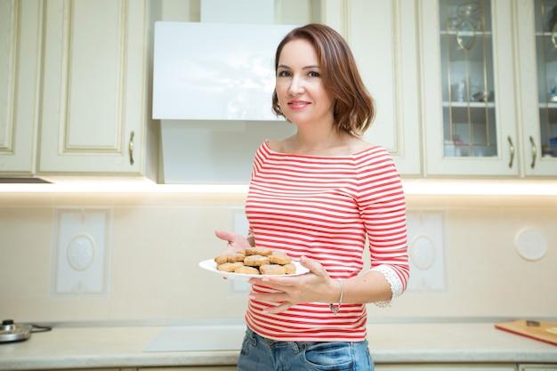 Piękna dorosła kobieta z ciasteczkami w dłoniach w kuchni