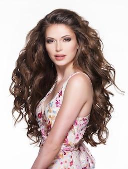Piękna dorosła kobieta z długimi brązowymi włosami kręconymi. modelka na białym tle