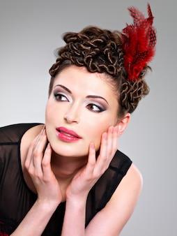 Piękna dorosła kobieta z fryzurą moda z czerwonym piórkiem we włosach