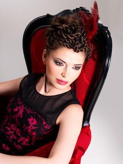 Piękna dorosła kobieta z mody fryzurę i czerwony fotel pozuje w studio