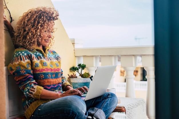 Piękna dorosła młoda kędzierzawa kobieta w pracy na tarasie w domu z laptopem