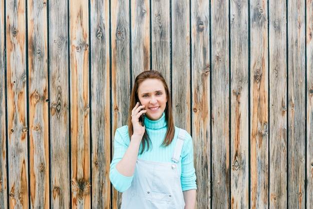 Piękna dorosła młoda kobieta rozmawia na smartfonie z drewnianym tłem