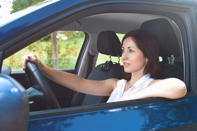 Piękna dorosła szczęśliwa kobieta jazdy samochodem w słoneczny letni dzień