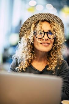 Piękna dorosła wesoła szczęśliwa kobieta pracuje z laptopem i bokeh kolorowym tłem - koncepcja technologii i miłych ludzi z inteligentną, nowoczesną pracą - okulary i blond kręcone włosy