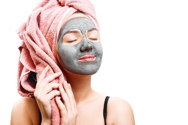 Piękna dość seksowna kobieta z czarną maską na białej ścianie, portret z bliska, odosobniony, różowy ręcznik na głowie, kobieta się uśmiecha, czarna maska na twarzy kobiety, cieszy się, emocjonalna rola płci
