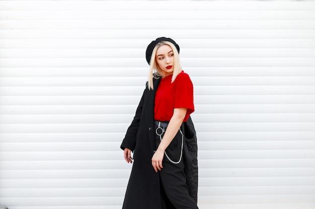 Piękna dość stylowa młoda kobieta w eleganckim berecie w czarnym płaszczu w czerwonej koszuli z czerwonymi seksownymi ustami w modnych czarnych spodniach w pobliżu nowoczesnej metalowej ściany na zewnątrz