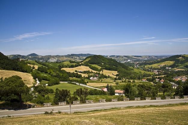 Piękna droga wzdłuż wiejskich domów z górzystym krajobrazem