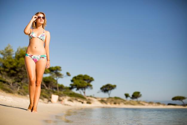Piękna, dysponowana i seksowna dziewczyna w bikini swimsuit pozuje na plaży przy latem