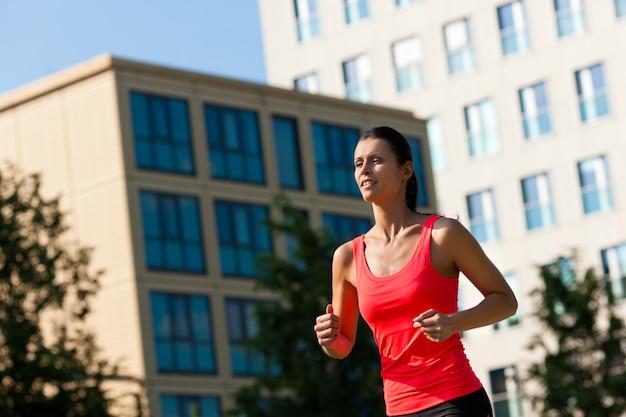 Piękna dysponowana kobieta jogging w mieście