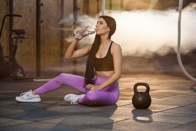 Piękna dysponowana kobieta pije wodę z plastikowej butelki po treningu w gym.