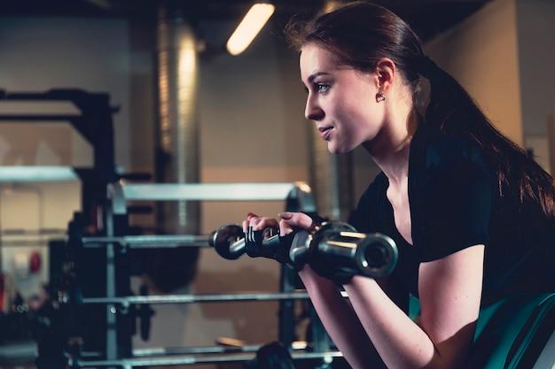 Piękna dysponowana kobieta robi ćwiczeniu w sprawności fizycznej centrum