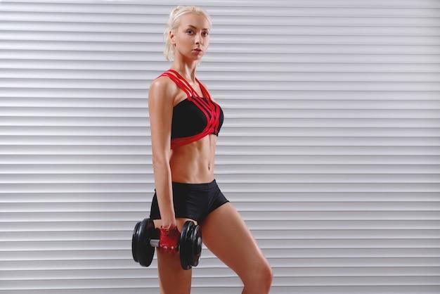 Piękna dysponowana młoda sportsmenka ćwiczy z dumbbells
