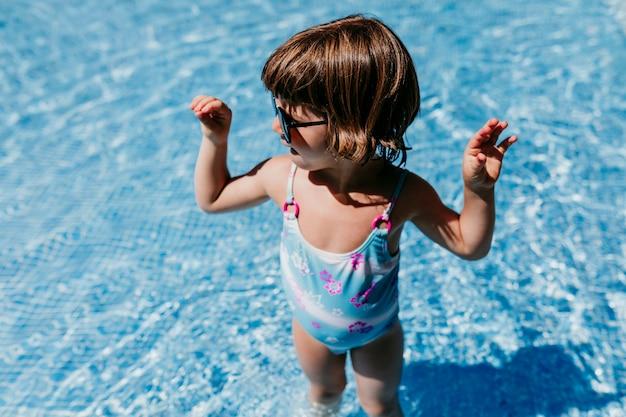 Piękna dzieciak dziewczyna przy basenem jest ubranym nowożytnych okulary przeciwsłonecznych. zabawa na świeżym powietrzu. koncepcja czasu letniego i stylu życia