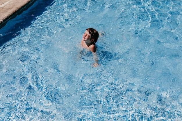 Piękna dzieciak dziewczyna przy basenem pływa i ma zabawę. zabawa na świeżym powietrzu. koncepcja czasu letniego i stylu życia
