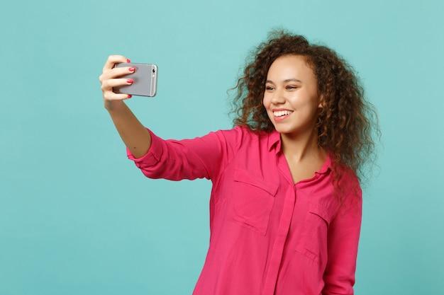 Piękna dziewczyna afryki w różowe ubrania dorywczo robi selfie strzał na telefon komórkowy na białym tle na tle niebieskiej ściany turkus w studio. ludzie szczere emocje, koncepcja stylu życia. makieta miejsca na kopię.