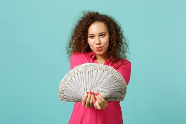 Piękna dziewczyna afryki w ubranie trzyma fan pieniędzy w banknotach dolara, pieniądze na białym tle na tle niebieskiej ściany turkus. koncepcja życia szczere emocje ludzi. makieta miejsca na kopię.