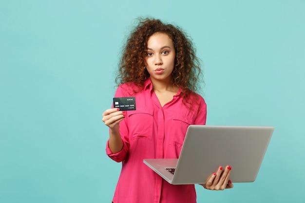 Piękna dziewczyna afryki w ubranie za pomocą laptopa, trzymając kartę kredytową bankową na białym tle na niebieskim tle turkusowym w studio. koncepcja życia szczere emocje ludzi. makieta miejsca na kopię.
