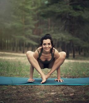 Piękna dziewczyna angażuje się w jodze w lesie