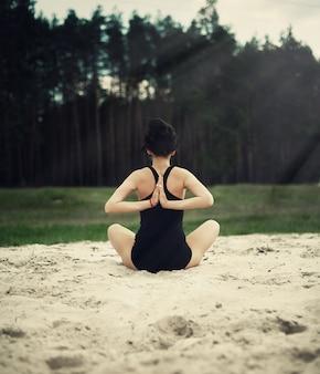 Piękna dziewczyna angażuje w joga w lesie na piasku