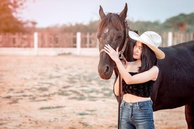 Piękna dziewczyna asia dbająca o swojego konia z miłością i troską.