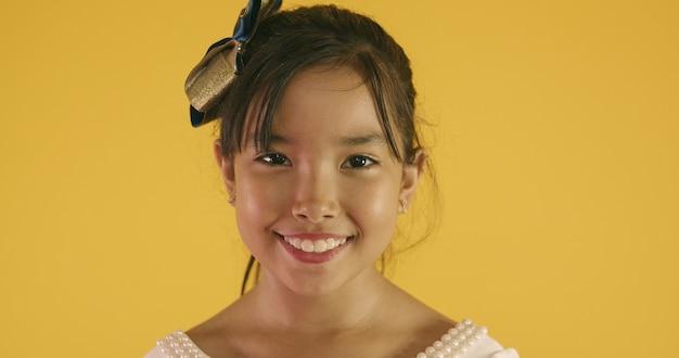 Piękna dziewczyna azjatyckich siedzi na żółtym tle. szczęśliwy azjatycki dziewczynka uśmiechając się.