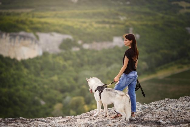 Piękna dziewczyna bawi się z psem, siwy i biały husky, w górach o zachodzie słońca. indyjska dziewczyna i jej wilk